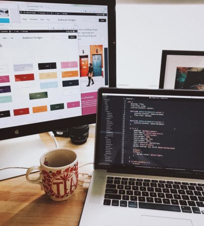 An image of a desk with a monitor with a design system visible and a laptop with front-end css coding visible.